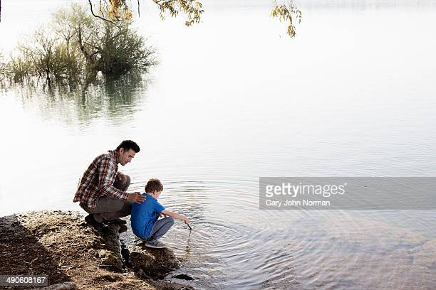 Dad and young son at water's edge