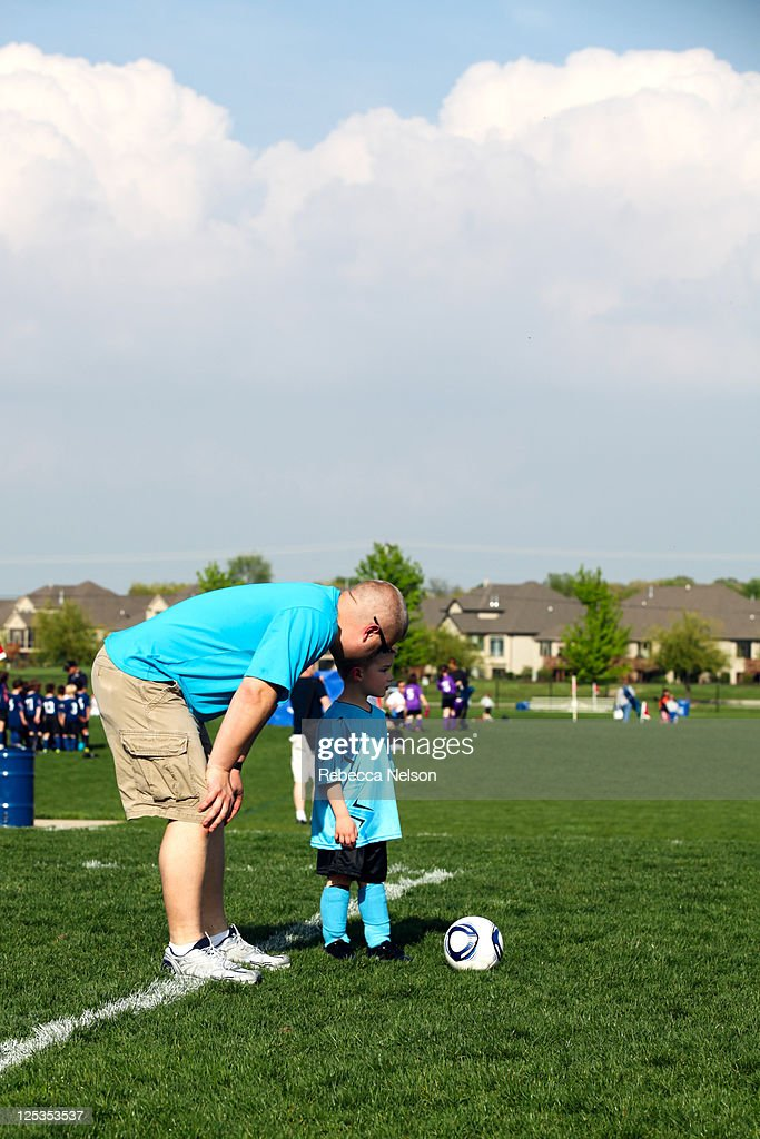 Dad coaching son in soccer : Stock Photo