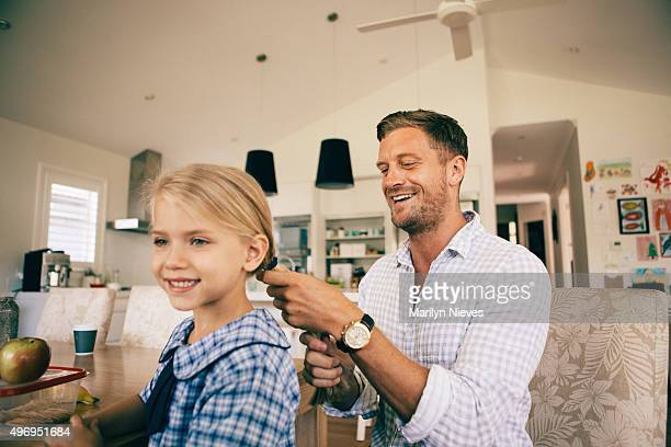 dad combing daughter's hair for school
