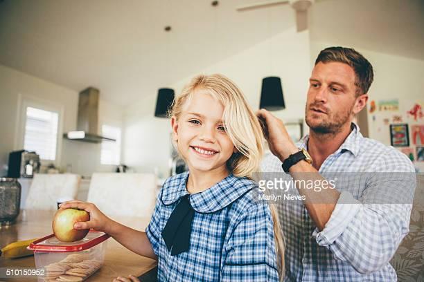 dad combing daughter's hair for school