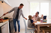 Dad cooking turns to mum with kids at the kitchen table