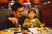 Dad & daughter enjoying meal in restaurant