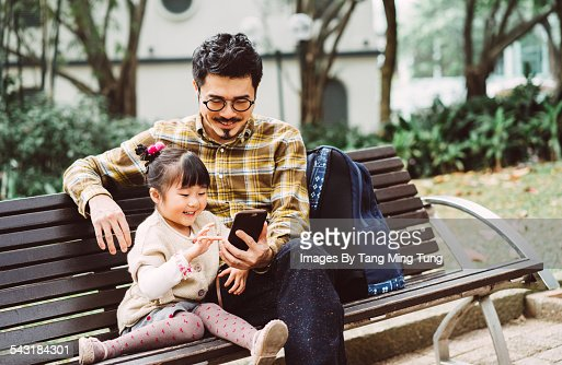 Dad & daughter using smartphone in park