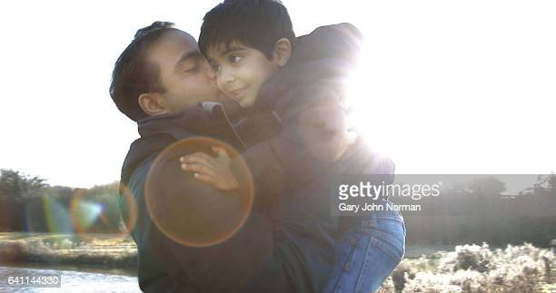 Dad embracing young son