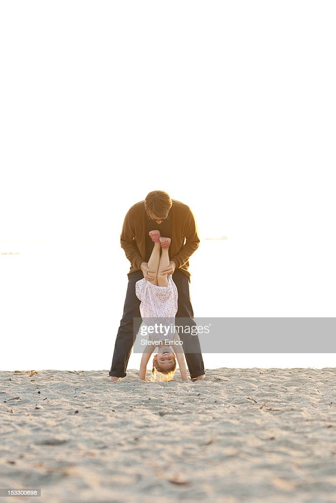 Dad helping his girl do a handstand at the beach : Stock Photo