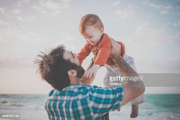 Dad Holding Baby Boy at Beach Sunset