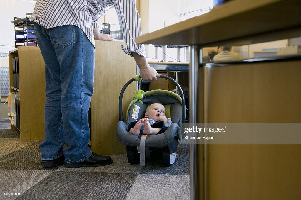 Dad holding baby in baby seat : Stock Photo