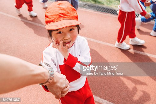 Dad holding hands with daughter on sports day