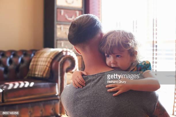 Dad hugging toddler daughter