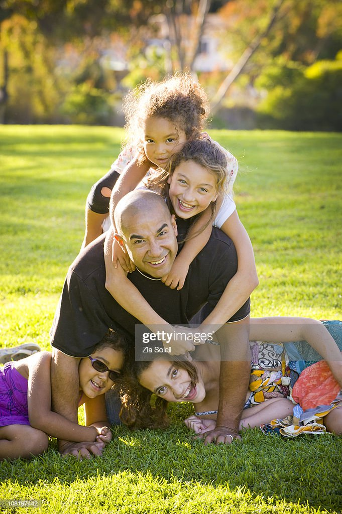 Dad in park wrestling with four girls : Stock Photo