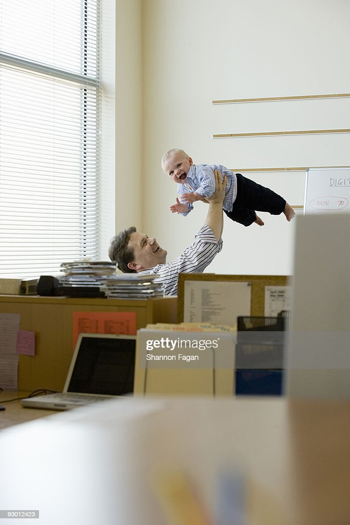 Dad lifting baby in office : Stock Photo