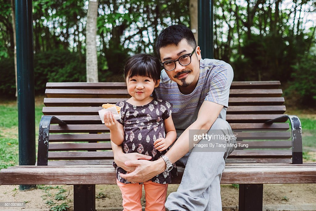 Dad & little girl smiling at the camera in park