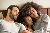 Interracial family, lying in bed, smiling as they watch television, in the privacy of their home