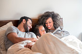 Interracial family, lying on the bed, tickling the little one, while everyone laughs merrily