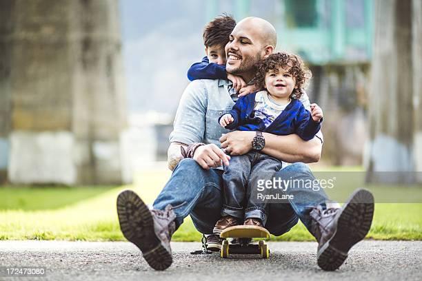 Père sur un skate dans un parc avec deux fils