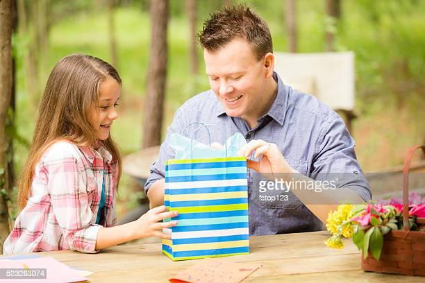 Père ouvre Fête des pères cadeau de fille en plein air.   Enfant parent.