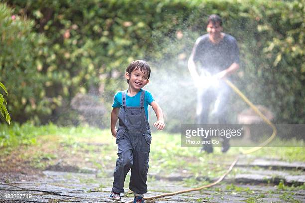 dad playing with a garden hose with his son