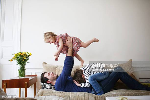 A dad playing with his children on a sofa