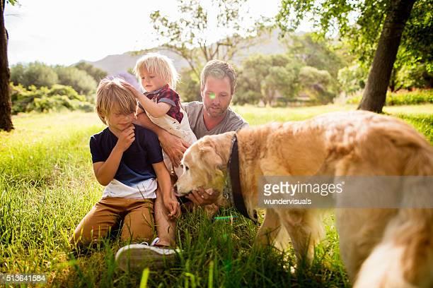 Papá juega con sus hijos y su perro lindo al aire libre