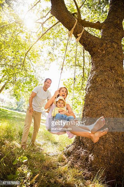 Dad pushing mom and their little girl on a swing