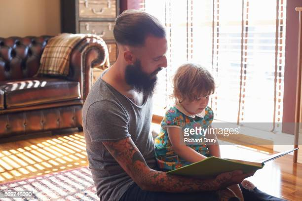 Dad reading a book to toddler girl