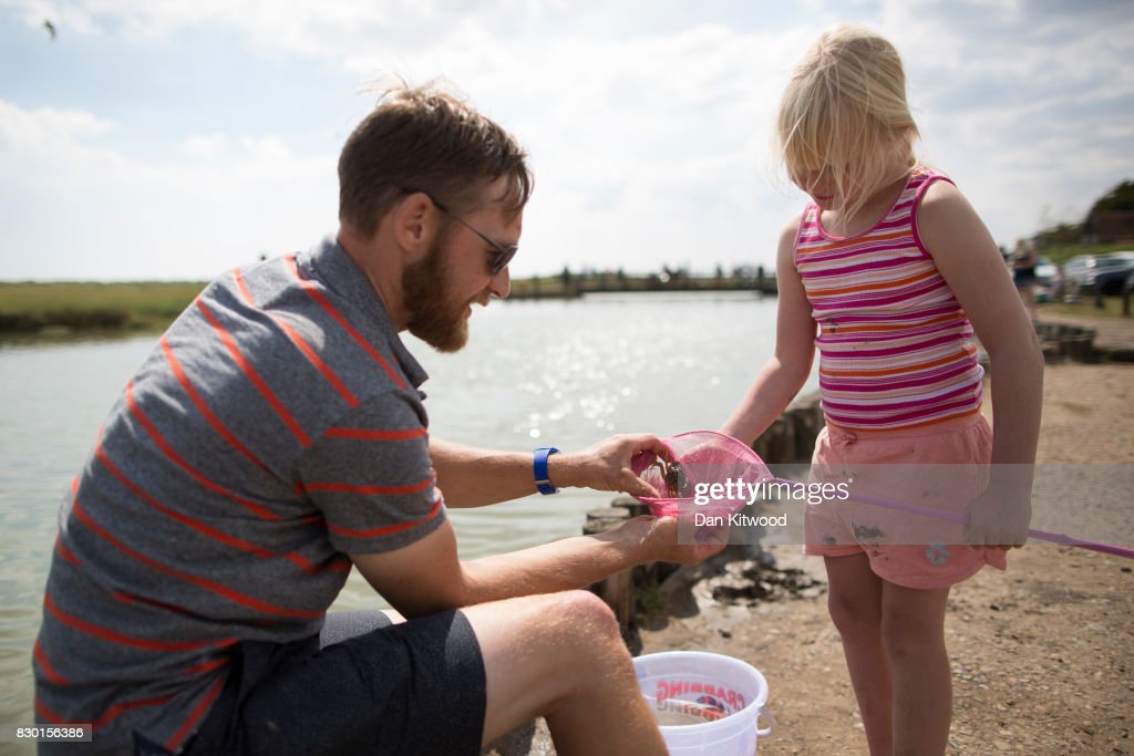 A dad shows his daughter a crab they caught on August 11, 2017 in Walberswick, England. Much of the country is expected to enjoy a sunny spell over the weekend after a period of unseasonably wet weather.