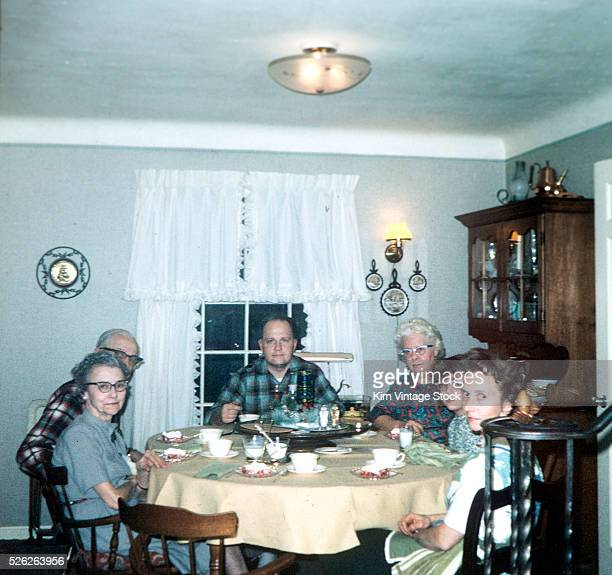 Dad sits at the head of the table with wife parents wife's parents and child