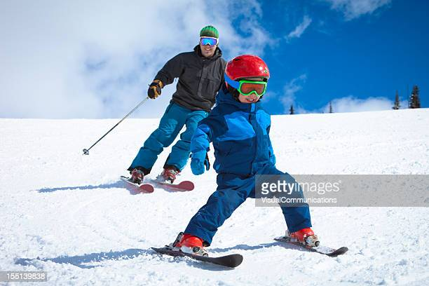 dad skiing with his small child.