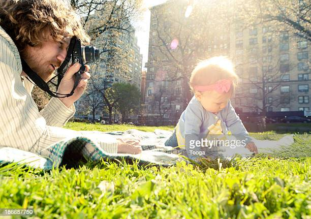Dad taking picture of baby with camera
