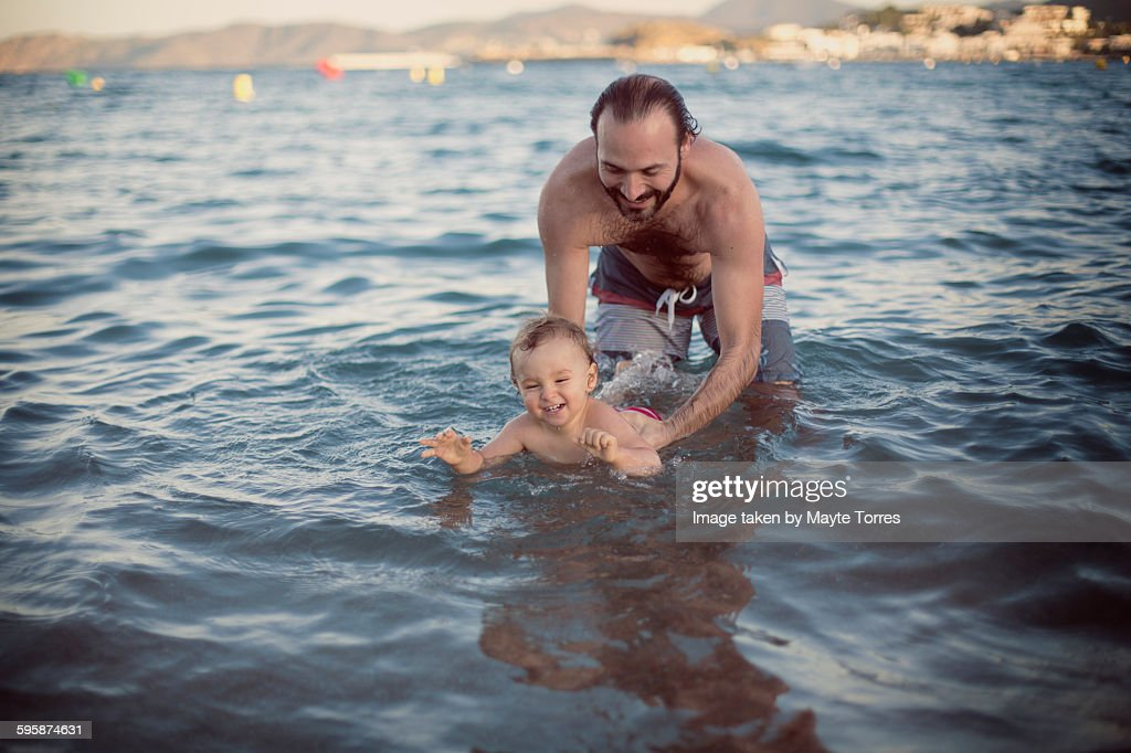 Dad teaching baby to swim
