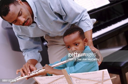 Dad teaching his son to plate the flute