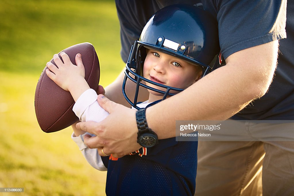 Dad teaching his young son how to play football : Stock Photo