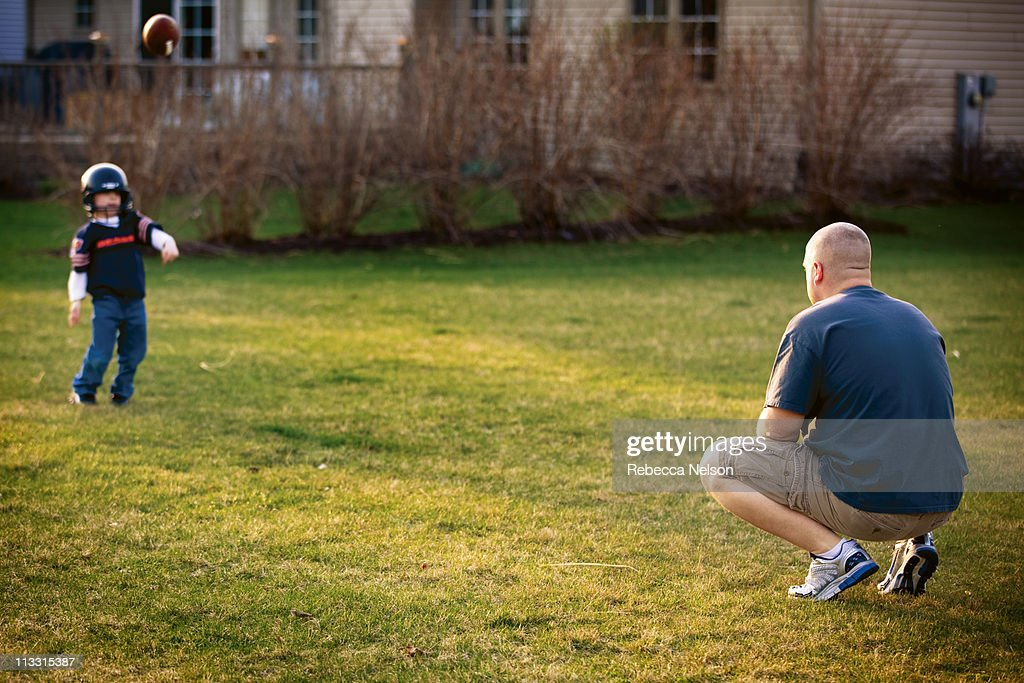 Dad throwing football with his young son : Stock Photo