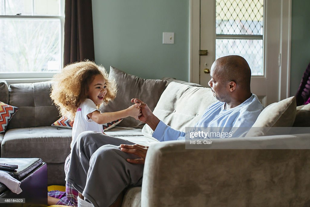 Dad thumb wrestling with daughter at home