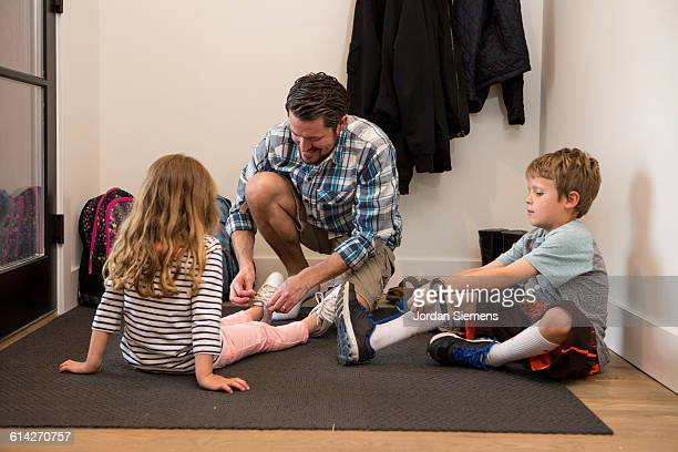 A dad tying his kids shoes.