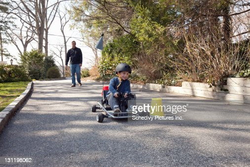 Dad watches adolescent son race go cart. : Stock Photo
