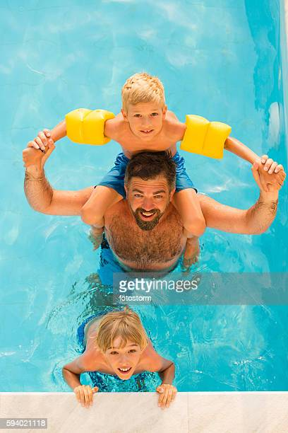 Dad with children in swimming pool