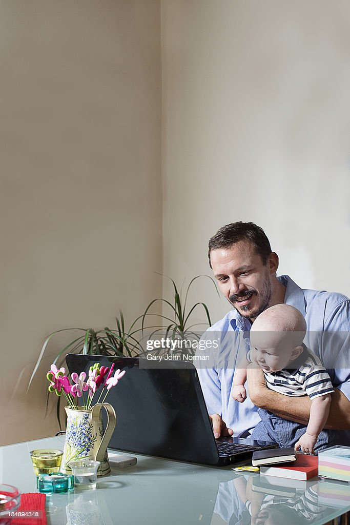 Dad working on laptop computer with baby : Stock Photo