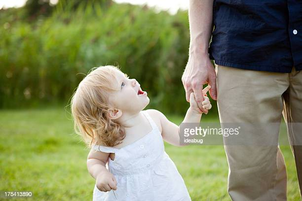 Daddy and Toddler Daughter Walking Outside Holding Hands