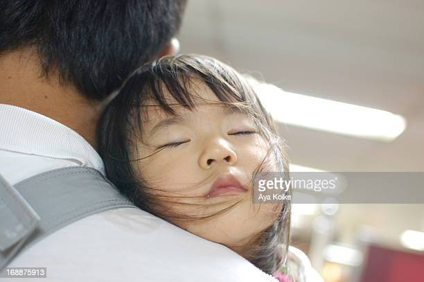 Daddy holding his daughter sleeping