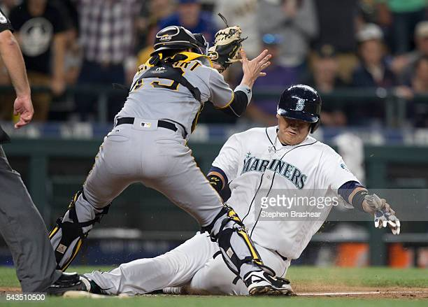 DaeHo Lee right of the Seattle Mariners slides into home plate before being tagged about by catcher Chris Stewart of the Pittsburgh Pirates during...