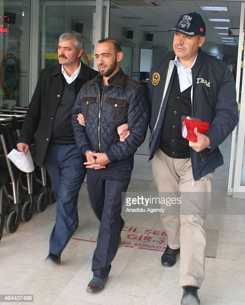 Daesh suspect among 30 others is seen as being escorted under arrest by two police officers to health check after an antiterror operation targeting...