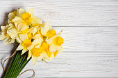 yellow daffodil bouquet of white wooden board.