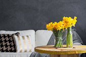 Daffodils on a table and white sofa in living room