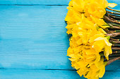 Daffodils on wooden background from above, copy space