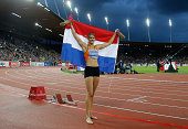 Dafne Schippers of the Netherlands celebrates with the Dutch national flag after winning gold in the Women's 200 metres final during day four of the...
