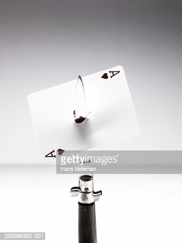Dagger cutting through Ace of Hearts card, close-up : Stock Photo
