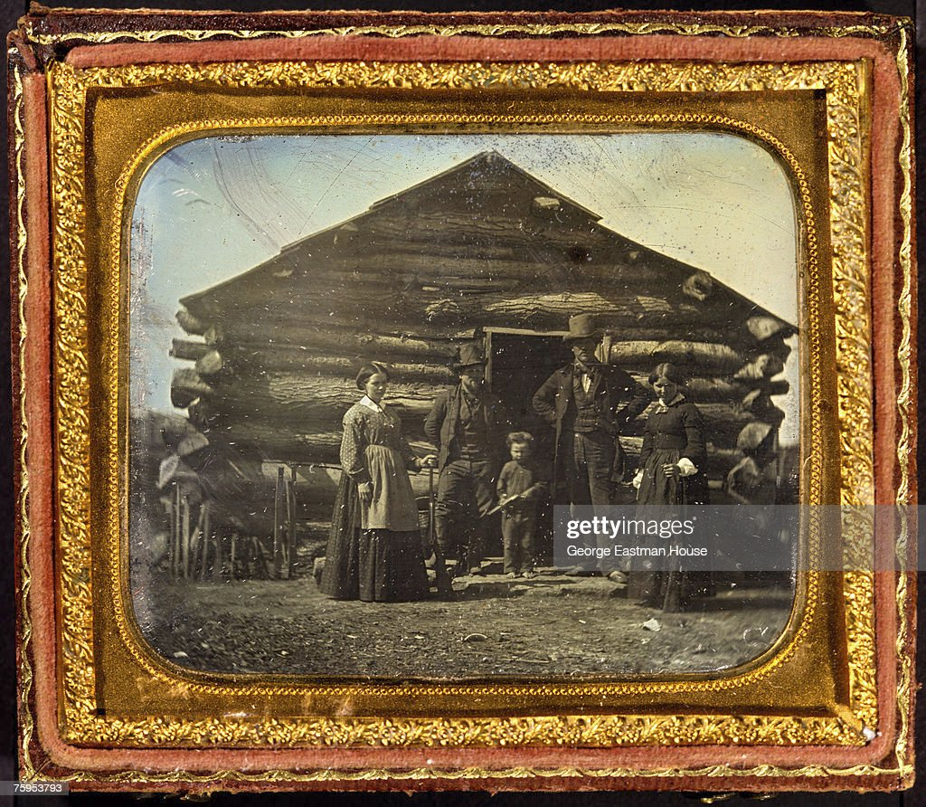 Daguerreotype in an ornate frame shows a family portrait of two women and a young child all of whom hold rifles as they pose with two men in front of...