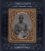 Daguerreotype of an AfricanAmerican soldier in Union cavalry uniform with cavalry saber in front of painted backdrop showing landscape 1863
