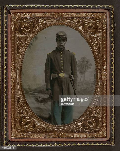 Daguerreotype of an AfricanAmerican soldier in Union uniform and Company B 103rd Regiment forage cap with bayonet and scabbard in front of painted...